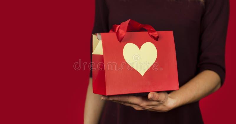 Une fille tient un cadeau avec un plan rapproché de coeur sur un fond rouge d'isolement Concept de Saint Valentin photos libres de droits