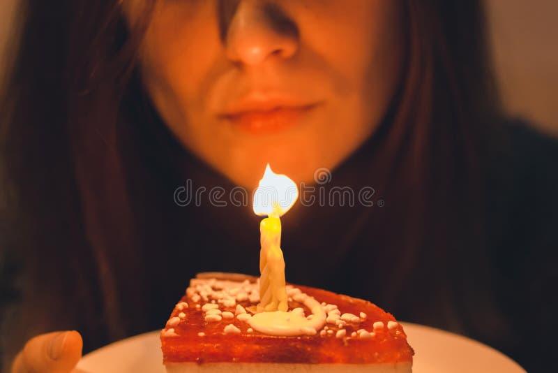 Une fille très belle souffle une bougie sur un gâteau qui se tient dans des ses mains sensibles image libre de droits