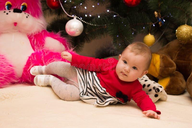 Une fille très petite s'assied sous un arbre de Noël avec les décorations colorées An neuf et arbre de Noël photo libre de droits