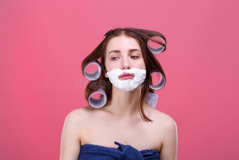 Une fille triste avec des bigoudis sur ses cheveux et mousse pour raser sur son visage, regards vers le bas avec un regard malheu photo stock