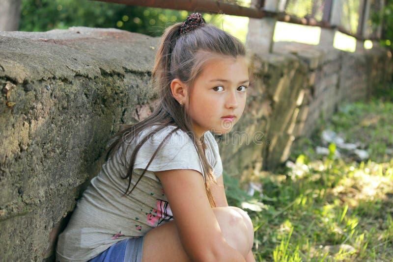 Une fille triste s'assied par le mur en pierre photo libre de droits
