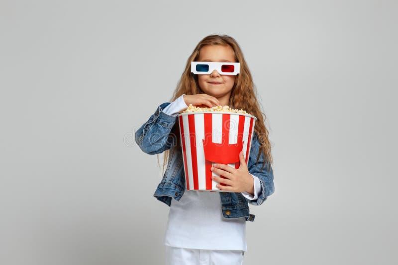 Une fillette portant des lunettes 3d bleu rouge s'amusant et tenant un seau à pop-corn images stock