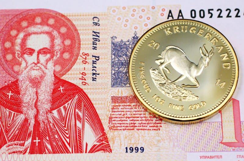 Une une fin bulgare de billet de banque de lev avec un Krugerrand d'or photographie stock