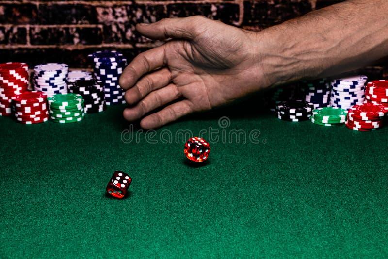 Une fin d'une paire de matrices roulées par quelqu'un sur une table de jeu felted verte Derrière la main de lancement il y a des  image libre de droits
