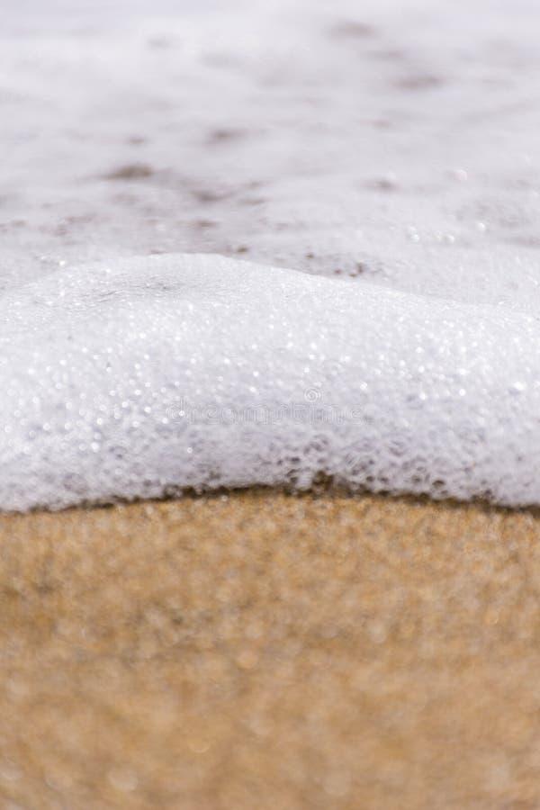 Une fin des vagues écumeuses un jour orageux contre la plage sablonneuse d'or Copiez la p?te photo stock