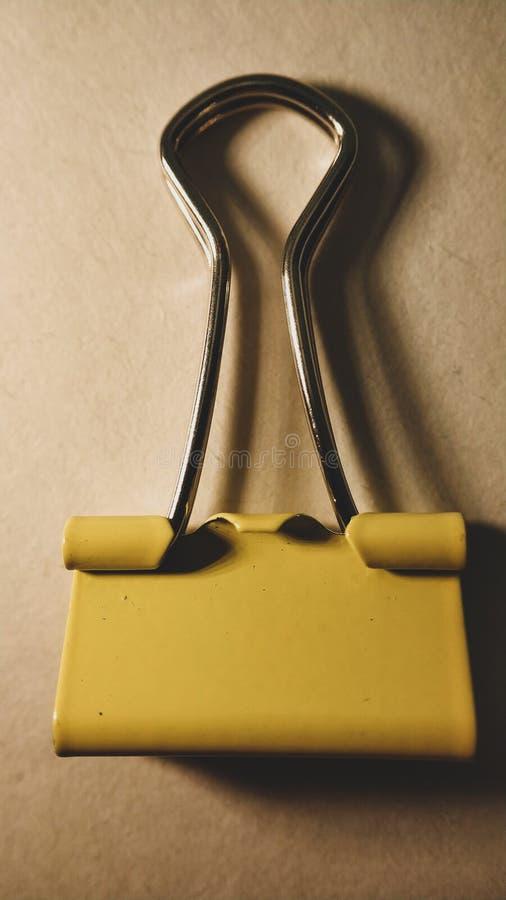 Une fin jaune de trombone sur le fond blanc image stock