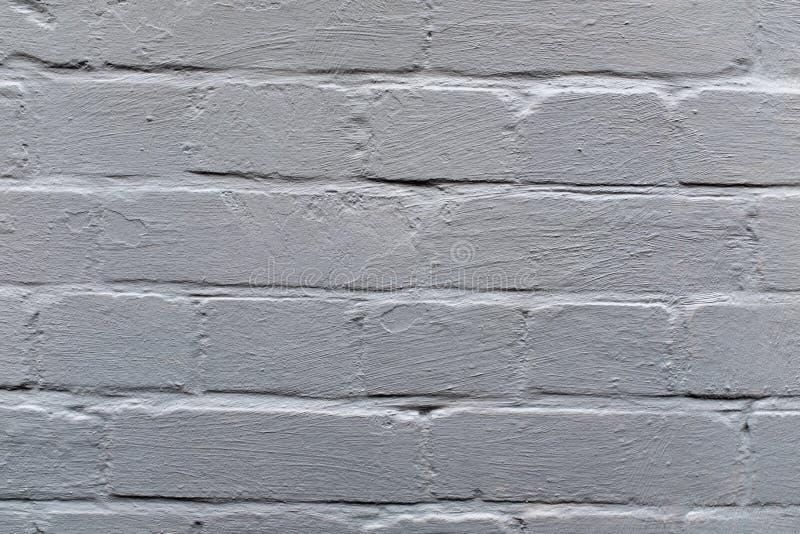 Une fin vers le haut de photo d'un mur de briques extérieur peint outre de blanc, surface avec le barbouillage de stuc, grand po photo stock