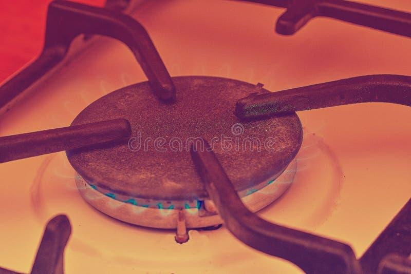 Une flamme bleue d'un brûleur de cooktop de gaz Brûleur de turbo de fourneau avec le plan rapproché brûlant de flamme photographie stock