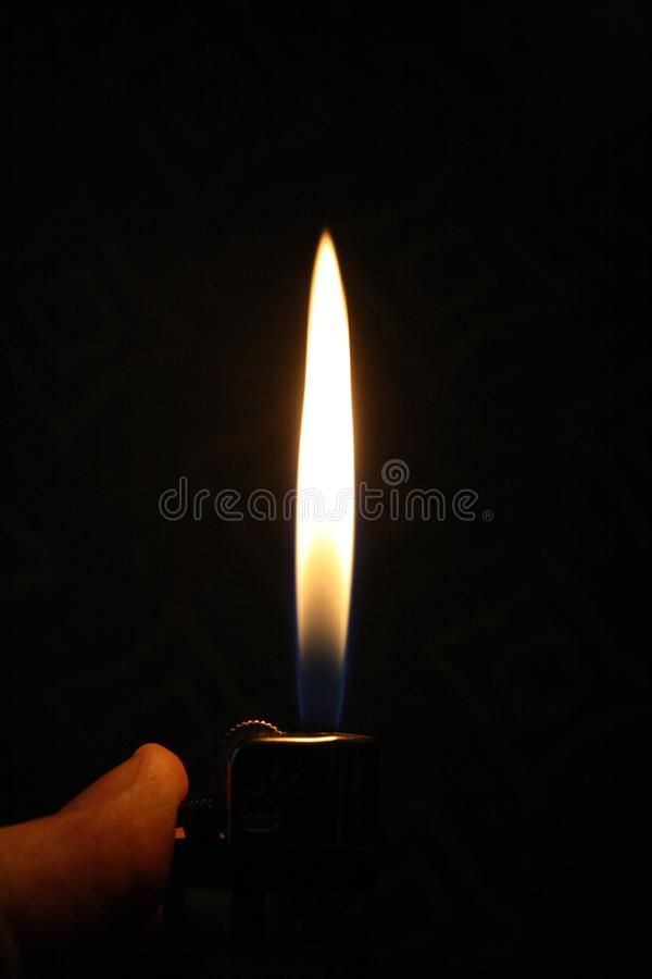 Une flamme plus légère allumée dans une chambre noire images stock