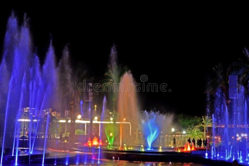 Une fontaine musicale rougeoyante la nuit Éclabousse de l'eau colorée images stock
