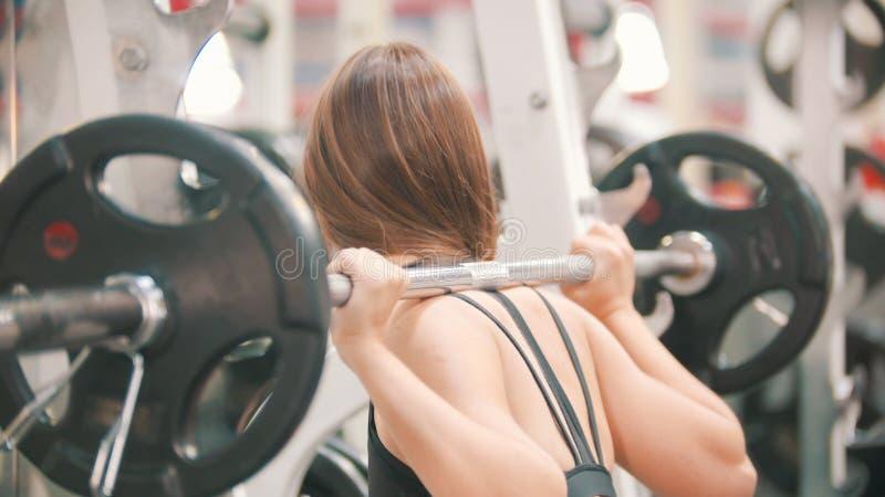Une formation de femme d'athlète dans le gymnase - s'accroupissant avec l'haltère la sur les épaules image stock