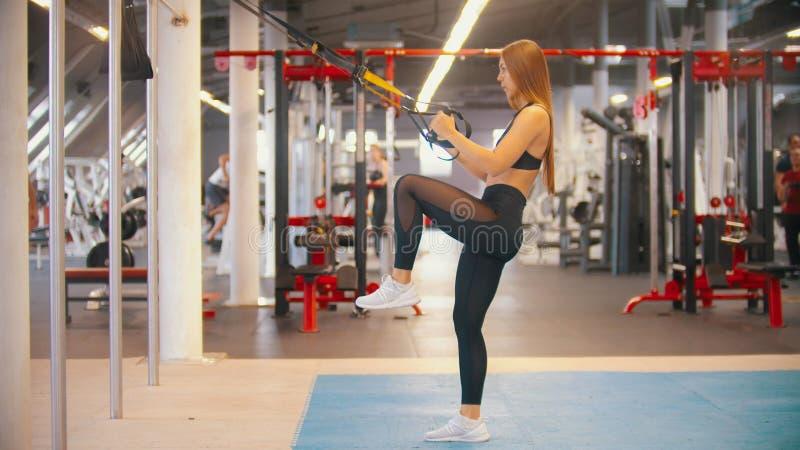 Une formation de femme d'athlète dans le gymnase - tenant les poignées et les augmenter son genou photographie stock libre de droits