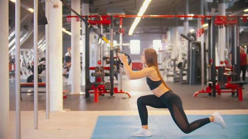 Une formation de femme d'athlète dans le gymnase - tenant les poignées et faisant vers le bas sur le genou photos libres de droits
