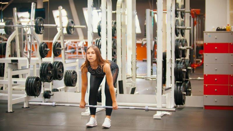 Une formation de femme d'athlète dans le gymnase - tenant un poteau de fer et se penchant vers le bas photographie stock
