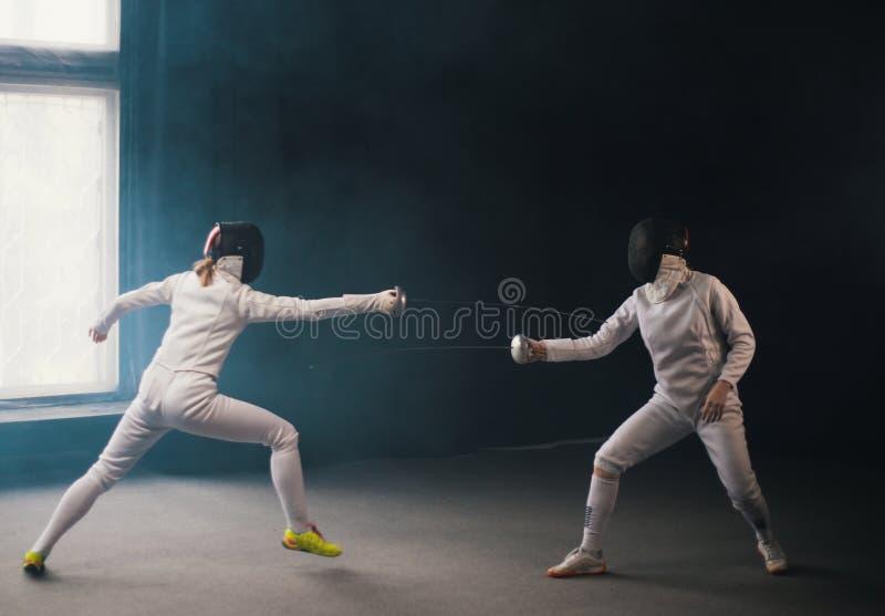 Une formation en clôture dans le studio - deux femmes en costumes de protection avec duel - se pointant des épées l'une sur l'aut photos stock
