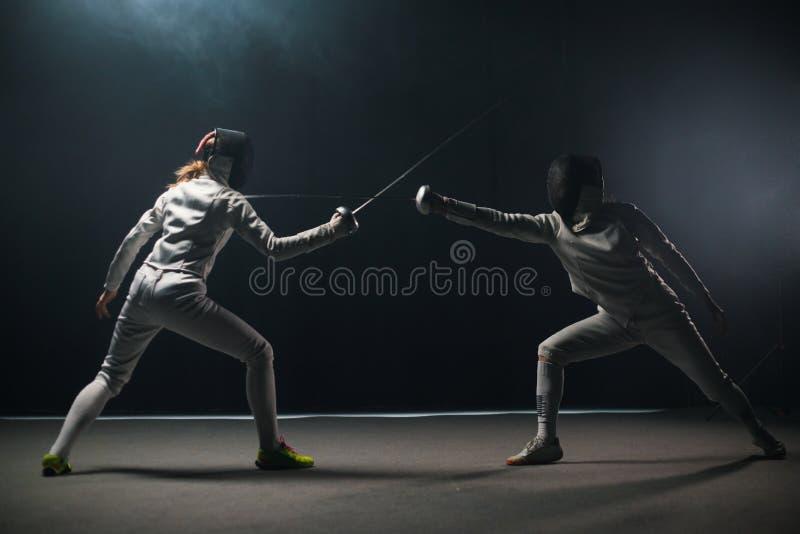 Une formation en clôture dans le studio - deux femmes en costumes de protection avec duel image libre de droits