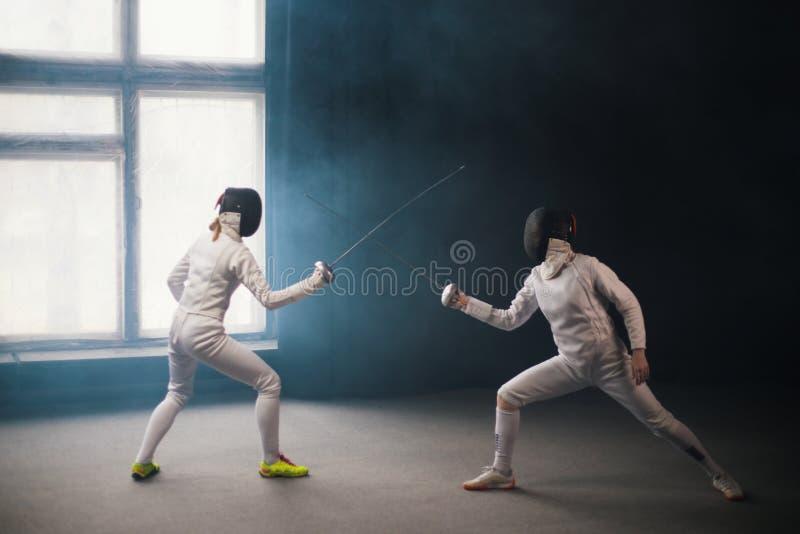Une formation en clôture dans le studio - deux femmes en costumes de protection blancs avec duel photographie stock libre de droits