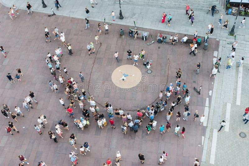 Une foule se réunit dans un secteur pedestrianised près de la place de château en tant qu'interprète de rue exécute des acrobatie photographie stock