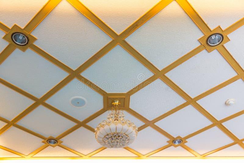 Une frontière d'or accrochante en verre de luxe de lampe sur le blanc et le ceil d'or photographie stock libre de droits