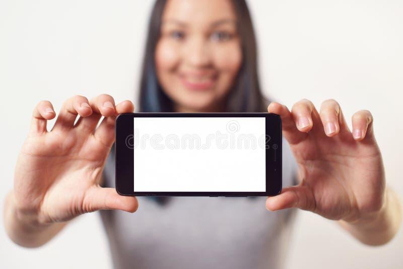 Une gentille femme tenant un smartphone avec un écran blanc vide avec deux mains horizontalement et souriant sur le fond blanc image stock