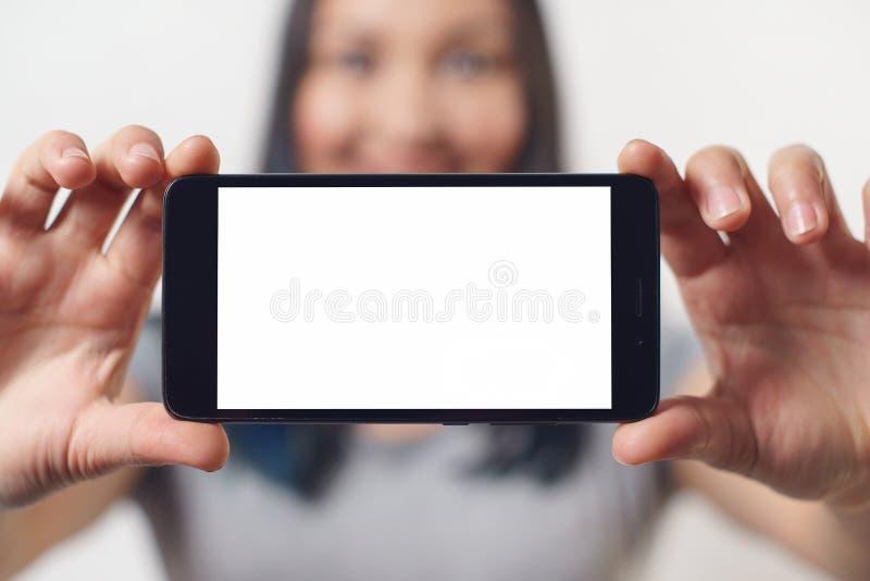 Une gentille femme tenant un smartphone avec un écran blanc vide avec deux mains horizontalement et souriant sur le fond blanc image libre de droits