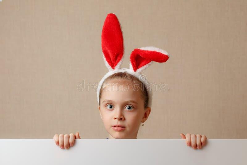 Une gentille petite fille regarde en raison d'une bannière vide dans laquelle vous pouvez insérer n'importe quel texte image stock