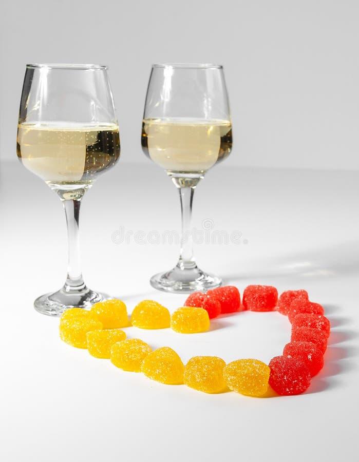 Une glace de vin blanc Sucreries multicolores sur un fond blanc photographie stock libre de droits