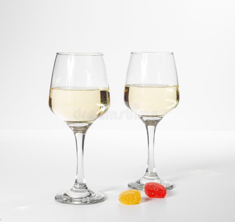 Une glace de vin blanc Sucreries multicolores sur un fond blanc photo libre de droits