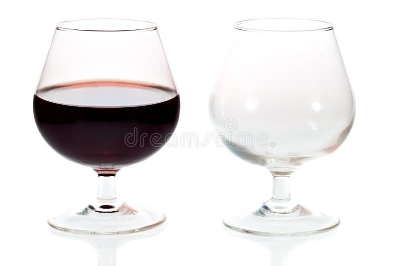 Une glace vide et pleine de vin rouge photo stock
