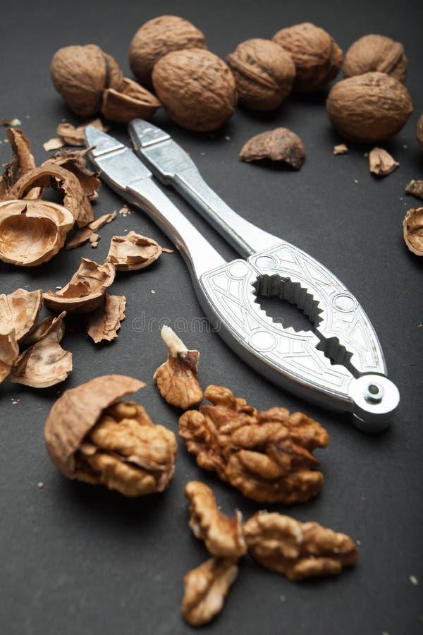 Une glissière des noyaux de noix avec un casse-noix rare sur un fond noir Nourriture saine et r?gime photos libres de droits