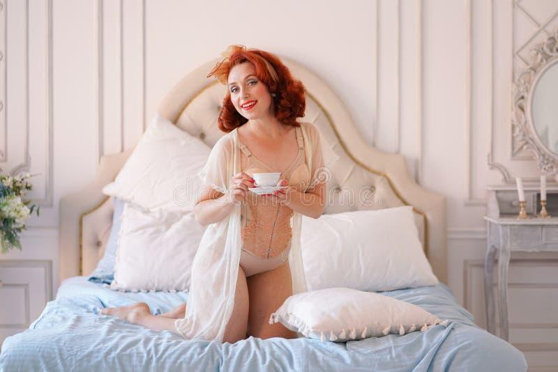 Une goupille luxueuse vers le haut de la dame habillée dans une lingerie beige de vintage posant dans sa chambre à coucher et ont photographie stock libre de droits