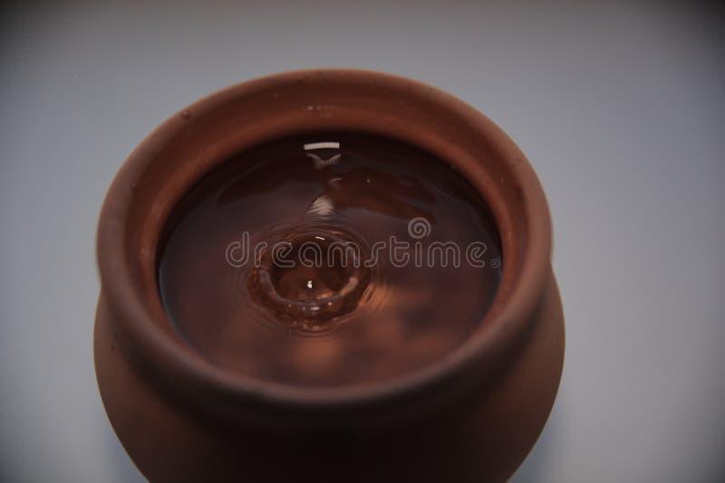 Une goutte de l'eau dans un pot d'argile image stock