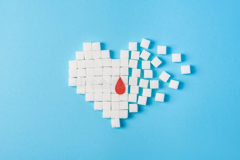 Une goutte de sang sur le coeur brisé fait de cubes blancs purs de sucre d'isolement sur le fond bleu, jour de diabète du monde photographie stock libre de droits