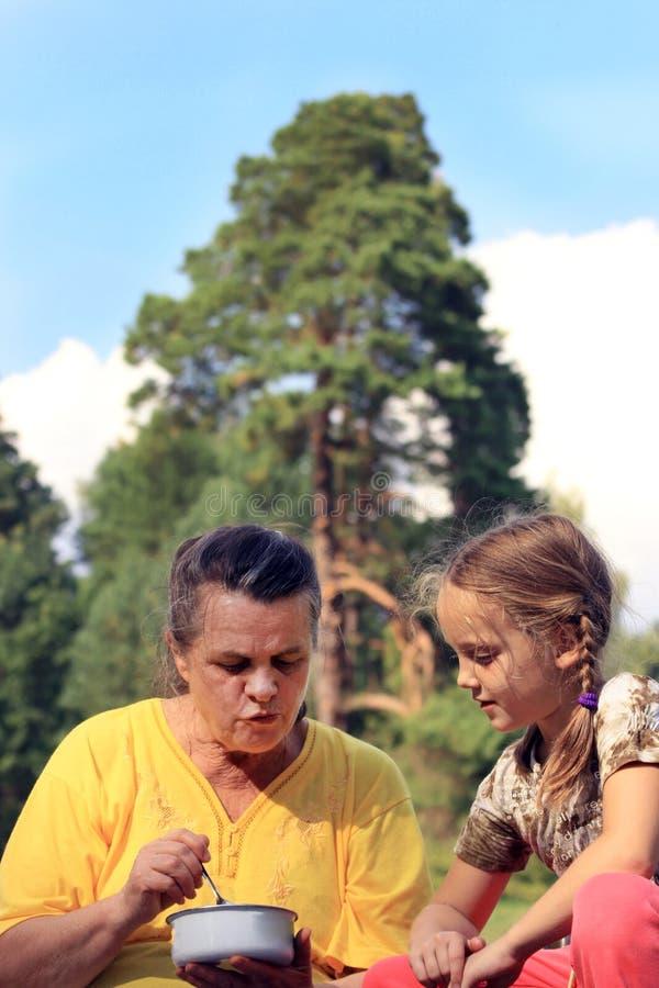 Une grand-mère alimente sa petite-fille par la cuillère de la cuvette dehors photographie stock