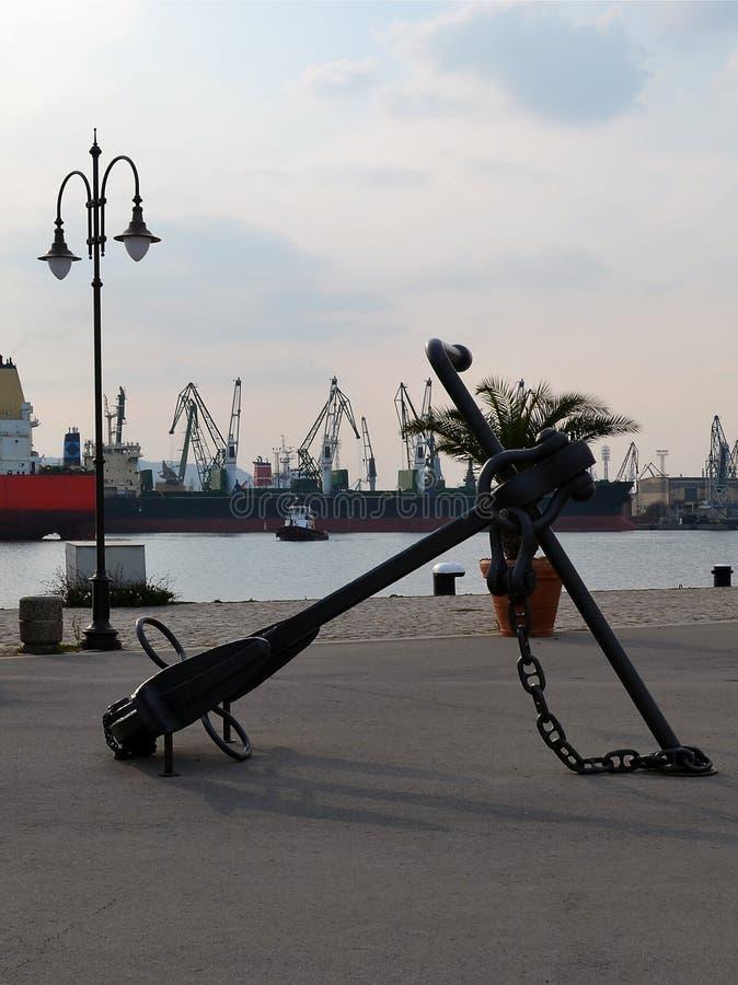Une grande ancre flottante orne la partie de marche du port, à l'arrière-plan sont le secteur de l'eau du port, des cargos et cra photos libres de droits