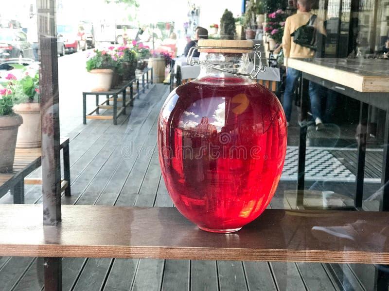 Une grande boîte lumineuse lumineuse ronde en verre transparente rouge avec un couvercle en bois, un récipient de jus doux délici images stock
