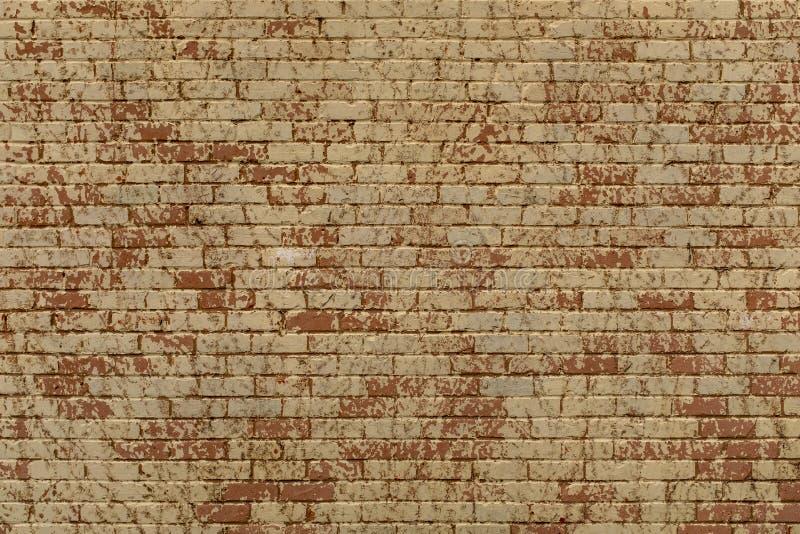 Une grande crème, un mur de briques peint rouge et orange, un idéal répété de modèle pour le fond ou une texture photo libre de droits