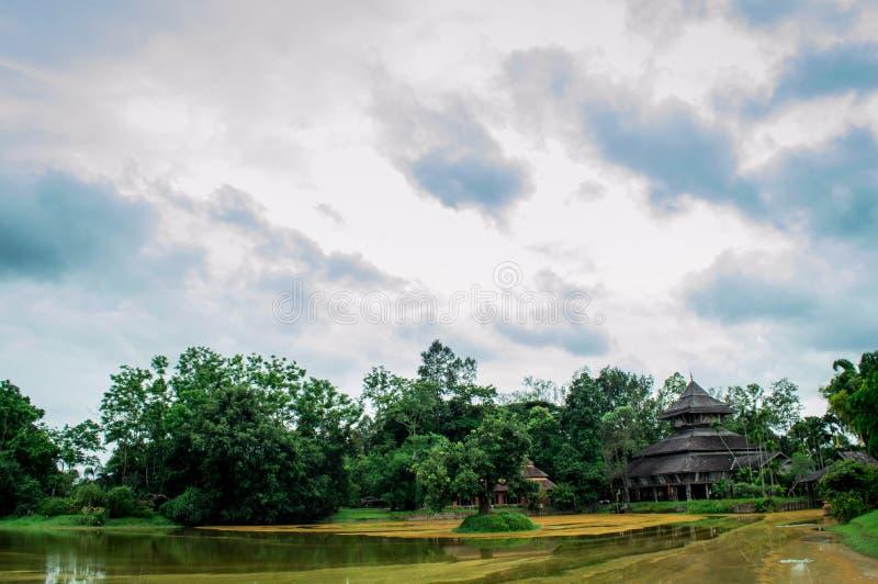 Une grande maison dans le jardin près de l'étang et du ciel bleu image stock