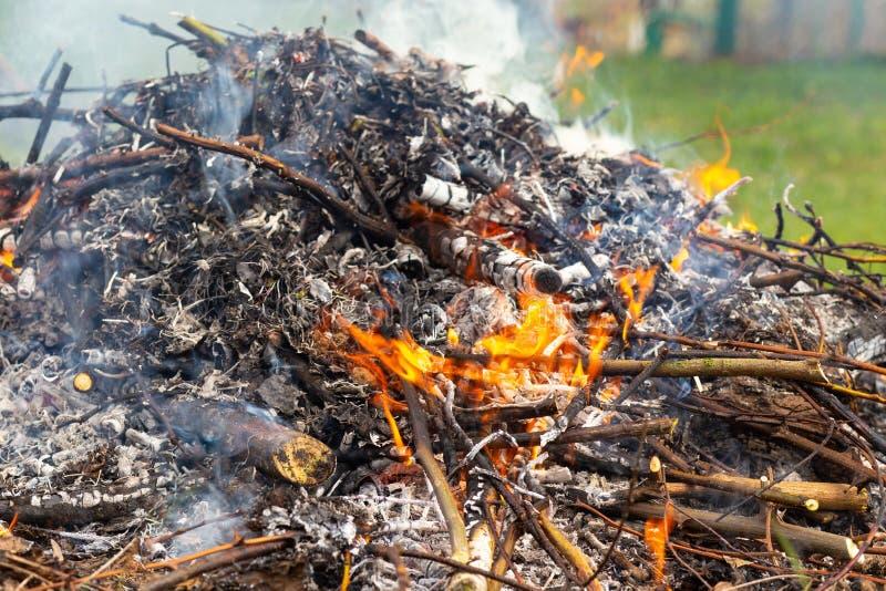 Une grande pile des branches et des feuilles br?lantes avec de la fum?e images stock