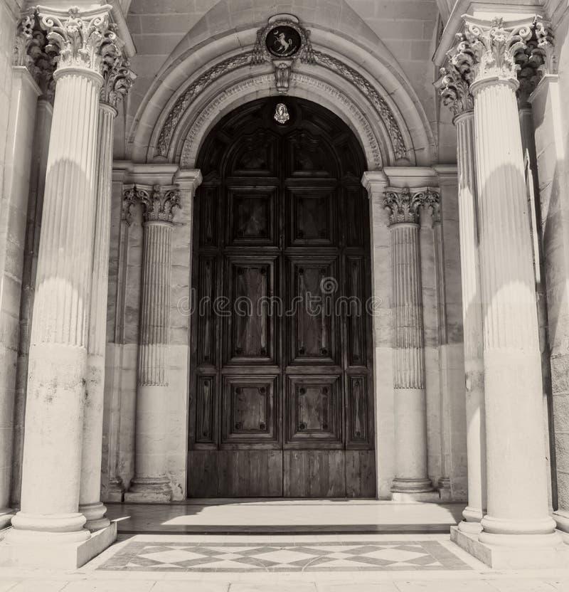 Une grande porte en bois avec les travaux en pierre gothiques photographie stock libre de droits