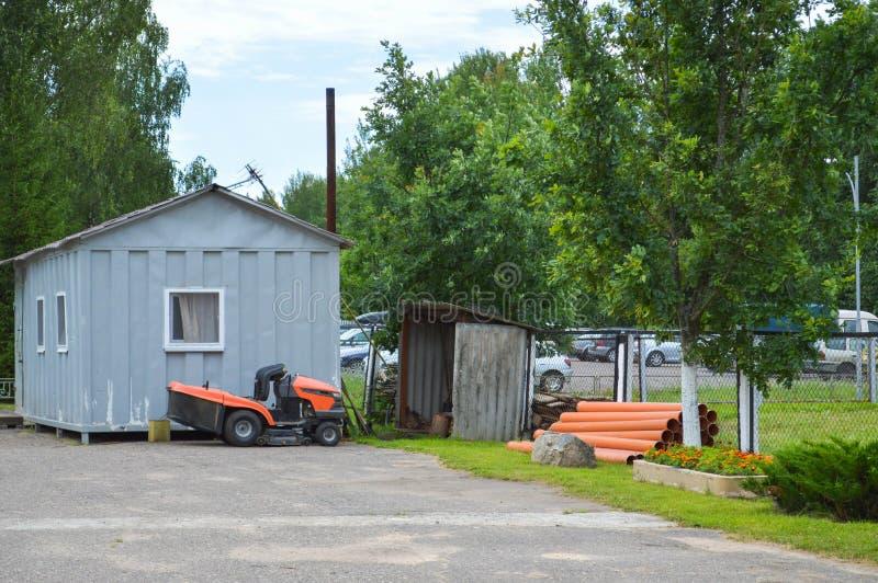 Une grande tondeuse à gazon agricole professionnelle, un tracteur de fauchage de pelouse avec l'herbe, supports près du hangar d' images stock