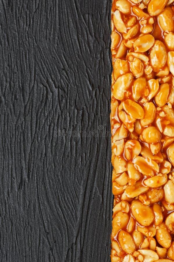 Une grande tuile d'or des arachides, une barre dans une mélasse douce sur un fond noir de texture Bonbons utiles et savoureux à K image stock