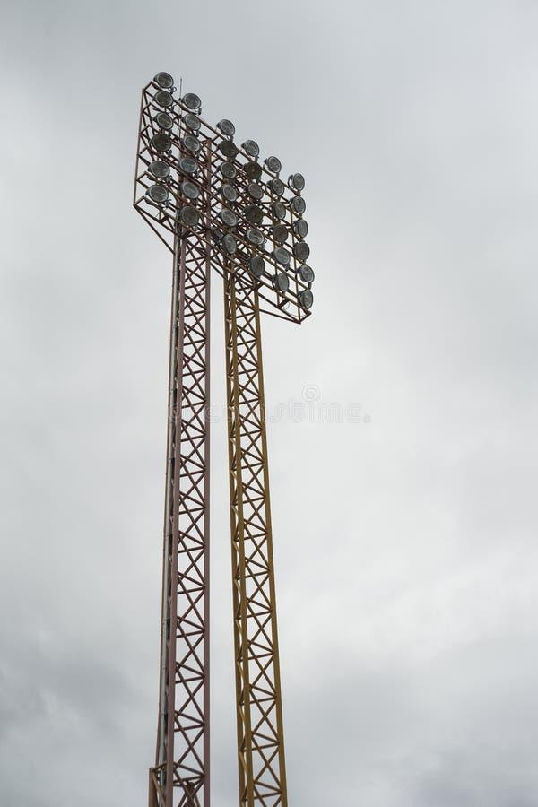 Une grands lumière de stade, courrier de lampe, industrie de l'électricité ou sports s'allumant contre le ciel nuageux à l'arrièr photos libres de droits