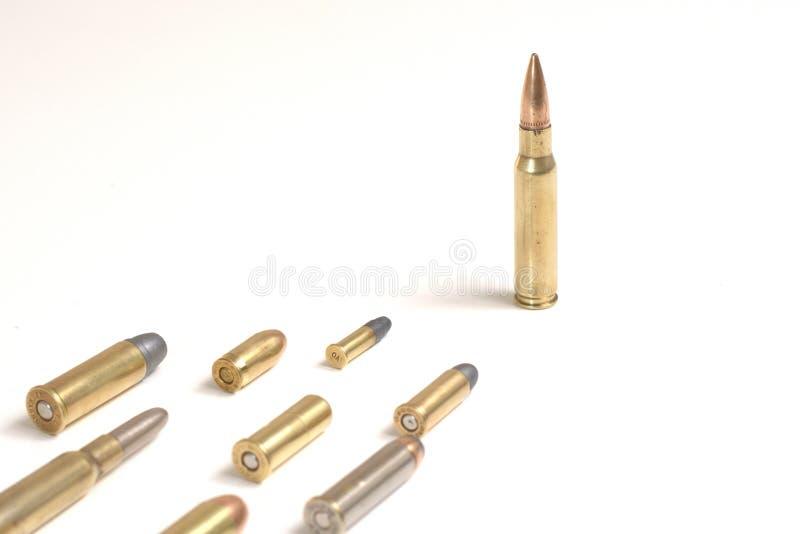 Une grosse balle 7. OTAN de 62 x 51 mm debout devant plusieurs autres balles posées sur une surface blanche photo stock