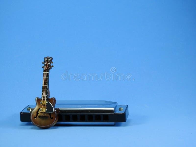 Une guitare électrique miniature se penchant sur un harmonica diatonique photos libres de droits