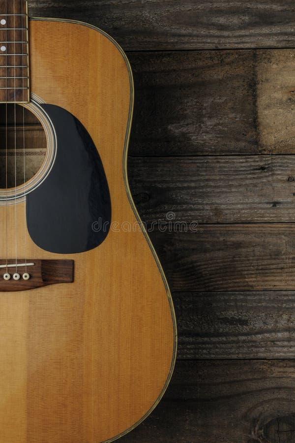 Une guitare acoustique sur le fond en bois grunge à employer comme couverture de livre pour un cours de guitare image libre de droits