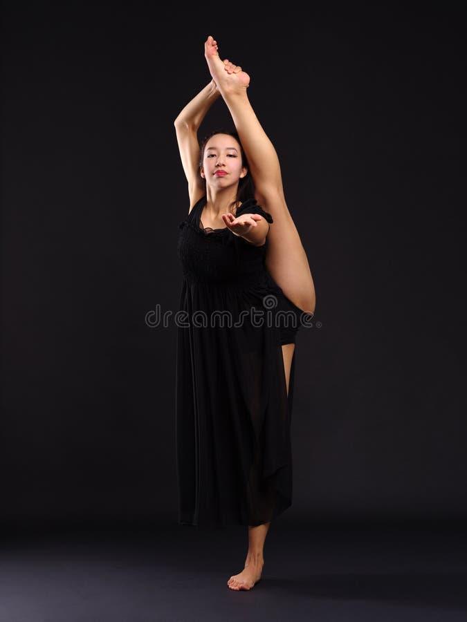Une gymnaste douée de jeune fille, supports sur une jambe dans une ficelle et prolonge sa main devant elle Fond noir photos libres de droits