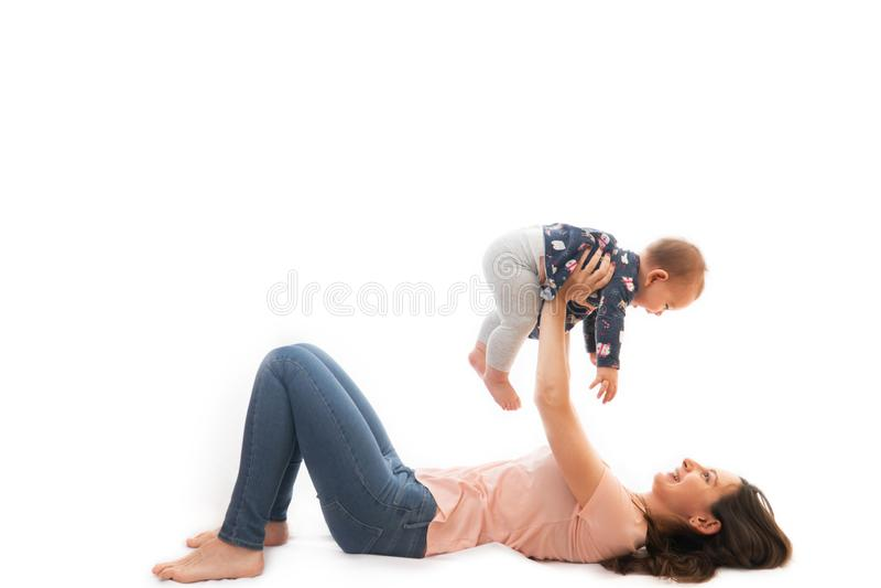 Une gymnastique de mère et de bébé, exercices de yoga d'isolement sur la forme physique blanche de fond photographie stock libre de droits