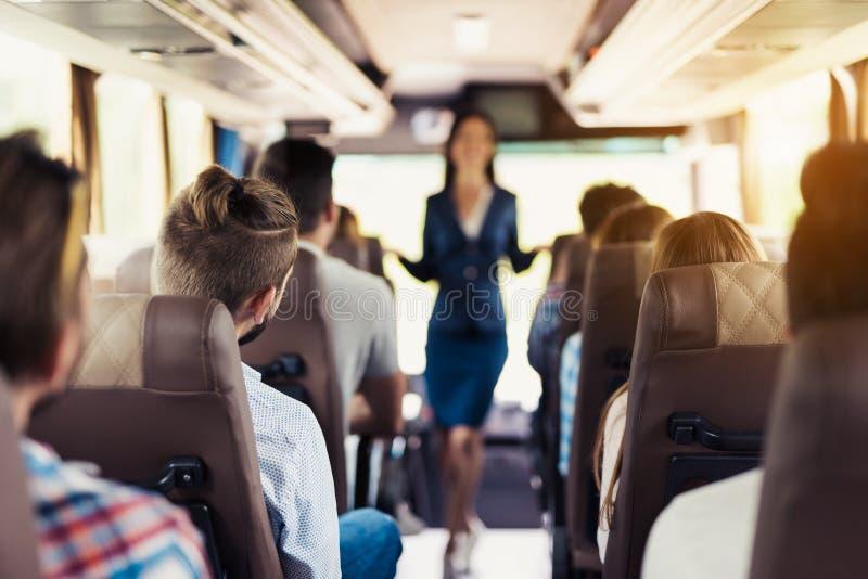 Une hôtesse pose sur l'autobus Il se tient entre les rangées des sièges sur lesquels les passagers s'asseyent images libres de droits