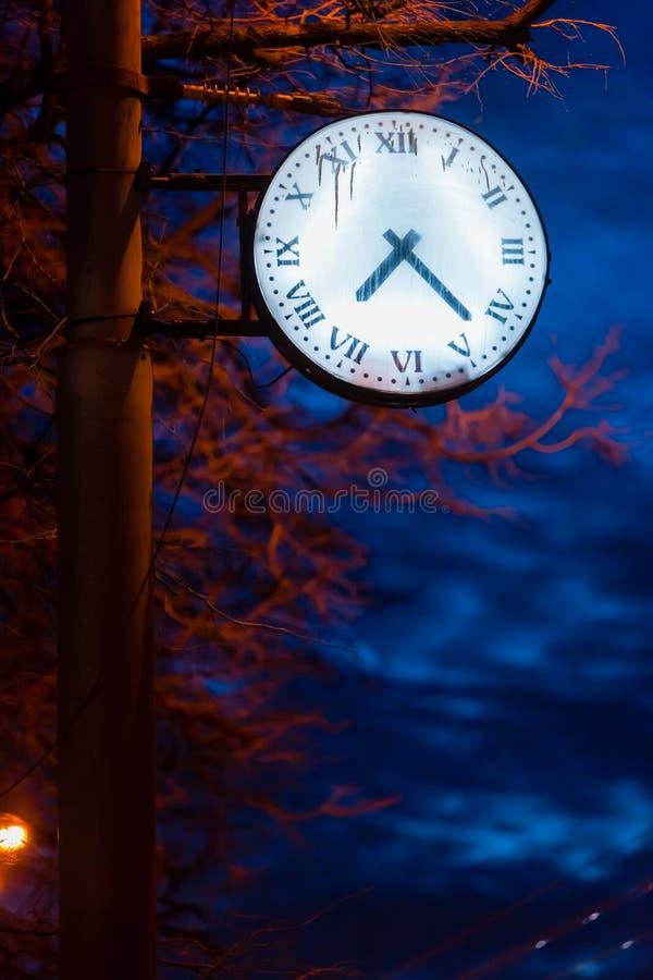 Une horloge avec un cadran rougeoyant sur un lampadaire de rue au crépuscule photo libre de droits